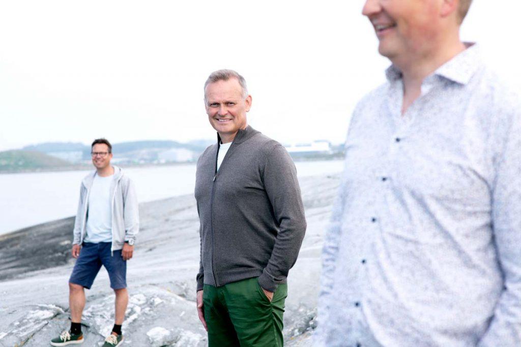 Three men walking by the sea. Efab